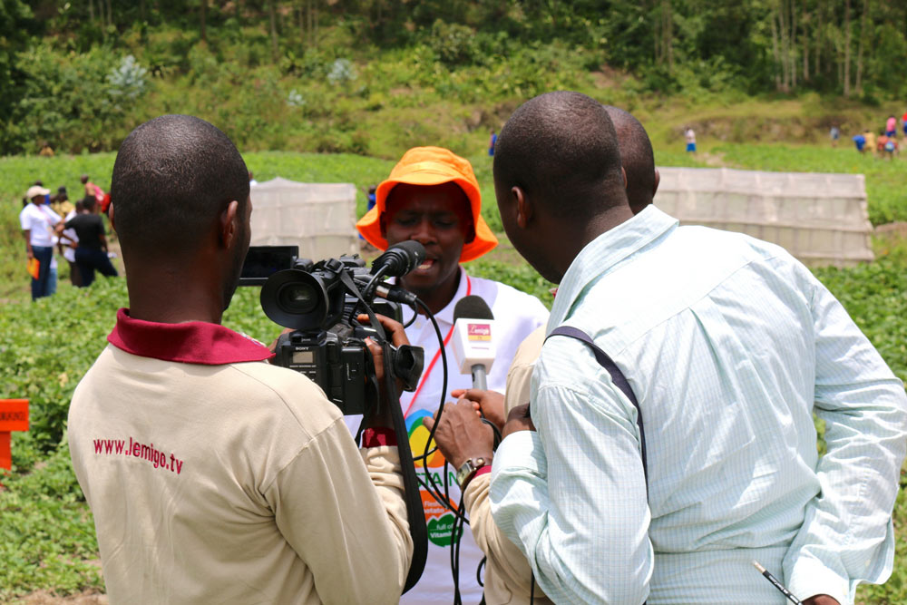 Jean Claude Nshimiyimana, Seed Systems Officer at CIP Rwanda discusses OFSP and SUSTAIN with the local media on a field trip to visit OFSP farmers, multipliers and processors